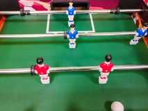 Friends having fun together playing foosball. Colleagues playing table football on break. Office people enjoying table soccer game royalty free stock photos