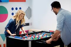 Friends having fun together playing table football Stock Photos