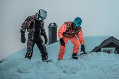 Friends having fun on top of the mountain while skiing/snowboarding. stock photo