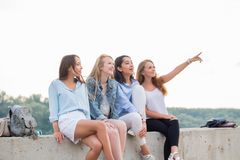 Friends Having Fun On Weekend, On Picnic Outdoors. Young Smiling People Sitting on concrete border stock image