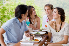 Friends Having Lunch. Four young adults enjoying a meal together on vacation royalty free stock photography