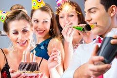 Friends having or new years eve birthday celebration Royalty Free Stock Photo