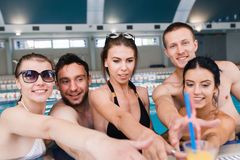 Friends having party and drinking buckets at a swimming pool Royalty Free Stock Image