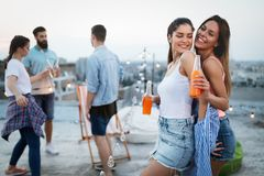 Friends having party on top of the roof. Fun, summer, city lifestyle and friendship concept stock photography