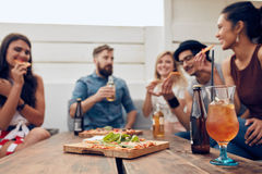 Friends having partying on rooftop. Group of happy young people standing together with drinks. Mixed race friends having rooftop party Royalty Free Stock Photography