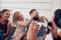 Friends having partying on rooftop. Group of happy young people standing together with drinks. Mixed race friends having rooftop party Royalty Free Stock Image