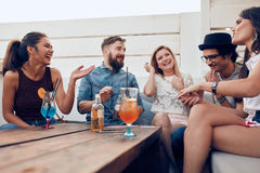 Friends having partying on rooftop. Group of happy young people standing together with drinks. Mixed race friends having rooftop party Royalty Free Stock Photo