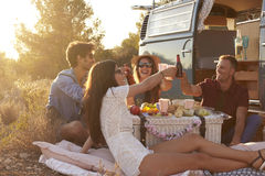 Friends having a picnic beside a camper van making a toast Royalty Free Stock Photo