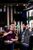 Friends having a pint and cheering. In a bar royalty free stock photography