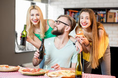 Friends having pizza party at home. Young friends dressed casually in colorful t-shirts having fun eating pizza and drinking beer at home Royalty Free Stock Photography
