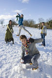 Friends having snowball fight in snowy field.  Royalty Free Stock Images