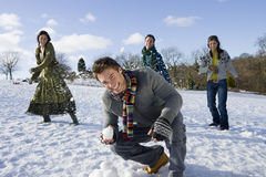 Friends having snowball fight in snowy field Stock Photo
