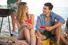 Friends having watermelon on shore at beach Royalty Free Stock Photography