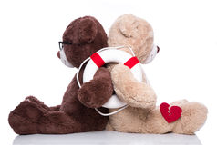 Friends help:  teddy bears back to back giving support isolated. On white background - also concept for teamwork or partnership Royalty Free Stock Photo