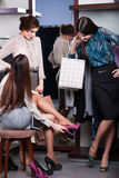 Friends help to choose an appropriate shoes Stock Photography