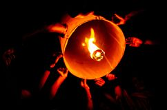 Friends help to float the lantern on a holiday. stock photos