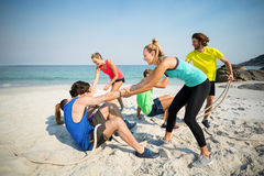 Friends helping man and woman while playing tug of war Stock Photo