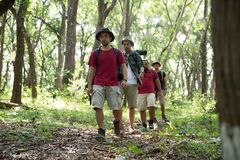 Friends hiking in outdoor summer activity. With backpack, people backpackers walking in the woods Stock Photos