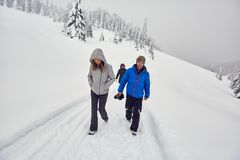 Friends hiking on a snowy trail stock photography