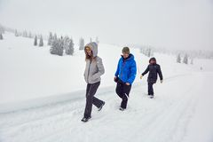Friends hiking on a snowy trail royalty free stock photography