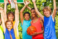 Friends hold arms up at basketball game. Standing outside during sunny summer day Stock Photo