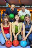 Friends hold ball for bowling. Three girlfriends squatting and behind stands two fellows  and everybody holds ball for bowling, focus on girls Stock Image