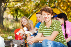 Friends hold marshmallow sitting on campsite Stock Photography