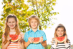Friends hold watermelon and eating together in row Royalty Free Stock Image