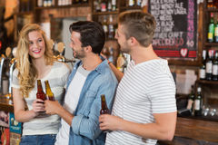 Friends holding beer bottles at pub. Happy friends holding beer bottles at pub Royalty Free Stock Images