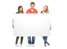 Friends holding blank poster. Three young people standing over white background Stock Photo