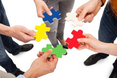 Friends holding colorful jigsaw pieces Stock Photo