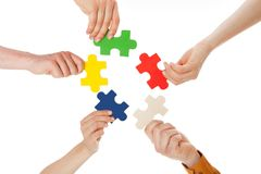 Friends holding colorful jigsaw pieces Royalty Free Stock Photos