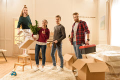 Friends holding different things for moving into new house Stock Photography