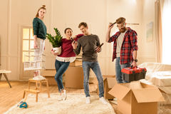 Friends holding different things for moving into new house Stock Image