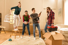 Friends holding different things for moving into new house Royalty Free Stock Image