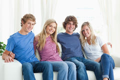 Friends holding each other as they look at the camera Stock Photos