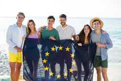 Friends holding European Union flag on shore at beach Royalty Free Stock Image