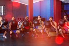 Friends holding exercise ball in gym Stock Image