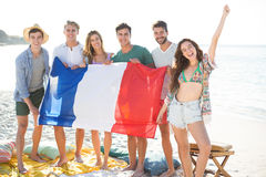 Friends holding French flag while standing at beach Royalty Free Stock Images