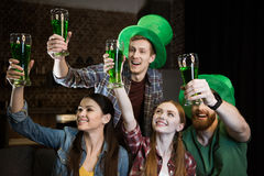 Friends holding glasses with beer on St. Patrick`s day celebration Royalty Free Stock Image