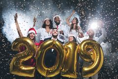 Friends holding 2019 golden balloons at New Year party. New Year party. Group of young friends carrying gold colored numbers 2019 and throwing confetti royalty free stock photo