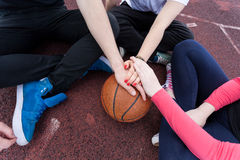 Friends holding hands on basketball. Group of friends sitting down and holding hands on a basketball Royalty Free Stock Photo