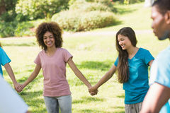 Friends holding hands in circle at park Stock Photo
