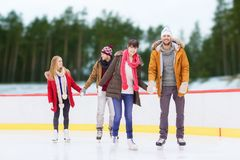 Friends holding hands on outdoor skating rink. Friendship, sport and leisure concept - happy friends holding hands on skating rink over outdoor background Stock Photos