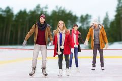 Friends holding hands on outdoor skating rink. Friendship, sport and leisure concept - happy friends holding hands on skating rink over outdoor background Stock Image