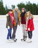 Friends holding hands on outdoor skating rink Stock Photos