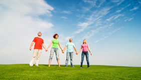 Friends holding hands outdoors Stock Images