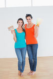 Friends holding paint brush and color swatches in a new house. Full length of two female friends holding paint brush and color swatches in a new house Royalty Free Stock Photo