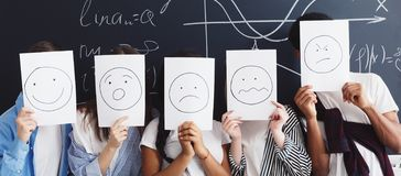Friends holding papers with painted emotions in classroom stock images