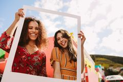 Friends holding picture frame outdoors stock photography